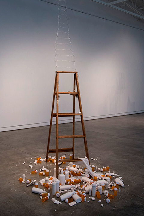 HOMAGE, installation of wooden ladder surrounded by plastic empty pill bottles and ceramic simulacra pill bottles by Susan Mollet